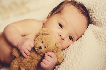 Een klein kind valt Een klein kind valt in slaap in een wieg met een speelgoed draagt ??in slaap in een wieg met een speelgoedbeer