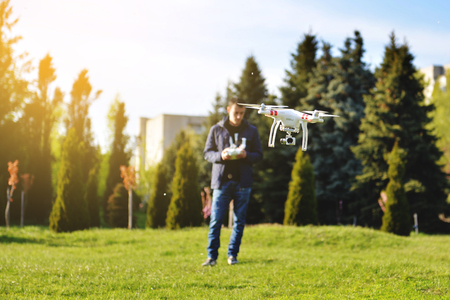 Man controls a quadrocopter. Selective focus on drone, men is blurred. Launching a quadrocopter in the park Stock Photo