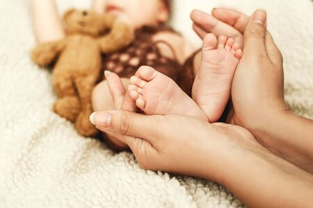 Baby legs. Legs newborn in parents hand Stock Photo