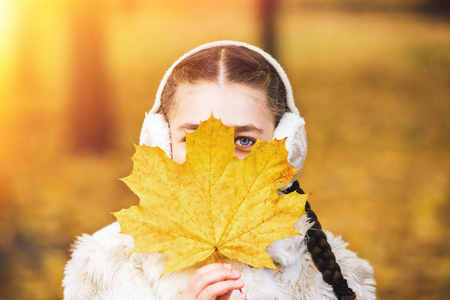 Beautiful girl covering her eyes with autumn leaf. Portrait of happy girl in park in fall. Stock Photo