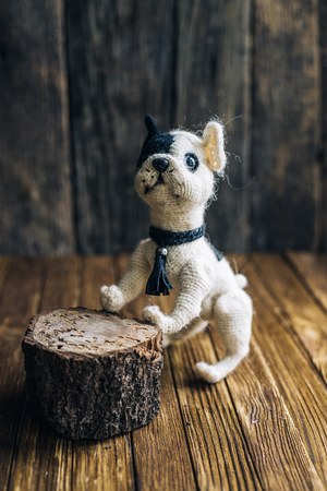 trabajo manual: Knitted dog French Bulldogs isolated on wooden background.