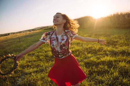 l hand: Girl enjoying nature on the field . The girl is joyful spinning with a wreath of flowers in her hands