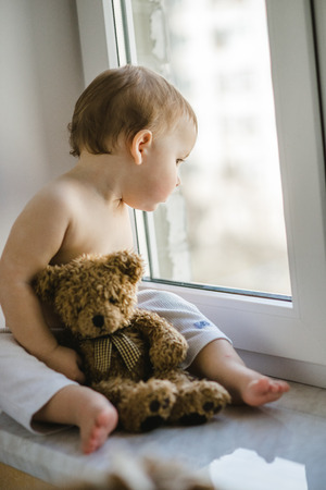 a little boy sitting by the window with a teddy bear in his hands Banco de Imagens