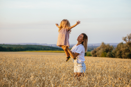 outsiders: beautiful young mother and her daughter having fun at the wheat field