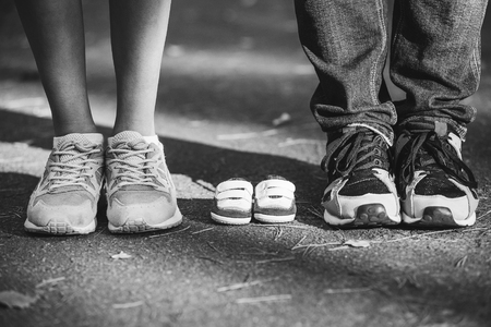 baby's feet: Waiting of baby. Little booties, sneakers near the feet of my father and mother. Pregnant woman, pregnancy, motherhood. Happy family. Moms, Dads and babys bootees. Family look. black and white photo Stock Photo