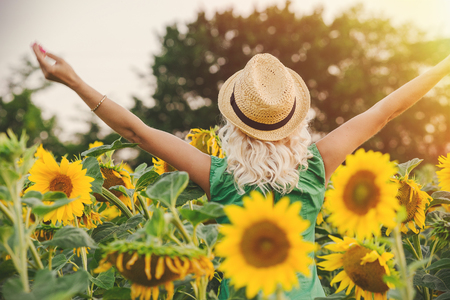 arms lifted up: A woman with long white hair and a hat lifted her arms up, rear view. The concept of freedom Stock Photo