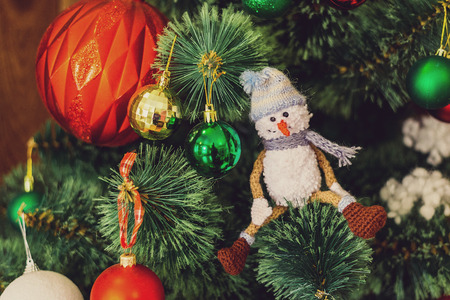Kknitted snowman on a branch of a Christmas tree. nitted Chrismas toys on green fir branches Reklamní fotografie