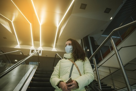 Person wearing protective mask against transmissible infectious diseases and as protection against pollution and the flu. Woman in a shopping center on an escalator