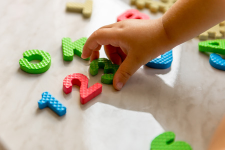 Colorful foam puzzle letters and numbers in kids hands on a light table. Baby puts puzzle of letters and numbers. Close-up