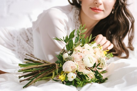 Portrait of a young charming bride in front of a wedding ceremony with a big beautiful bouquet in white lingerie. on a large bed. Close-up on a bouquet
