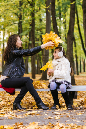 happy mother with her daughter in the autumn park
