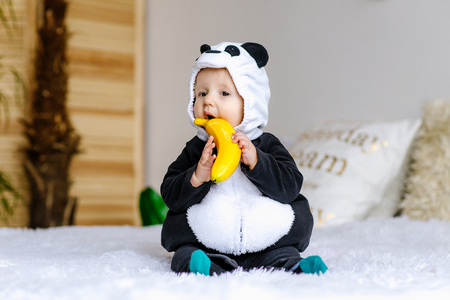 Cute little boy in bear costume Panda sitting on bed in room