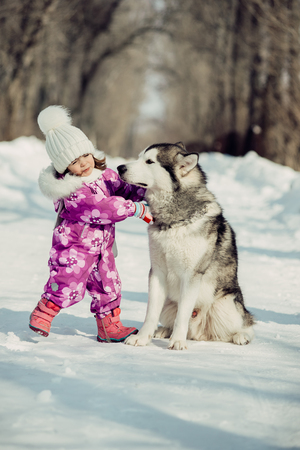 little girl with beautiful big dog in the forest in winter time