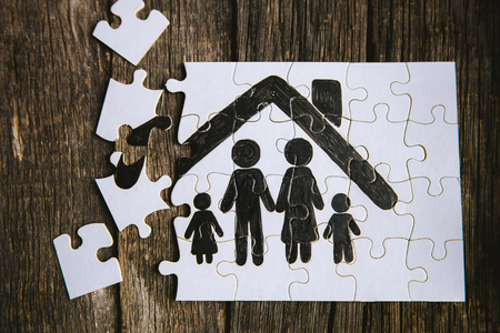 Family concept, puzzle. Father, mother, son and daughter under the roof of a house painted on a puzzle