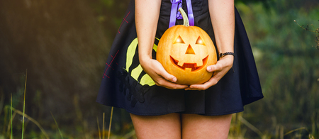 Fancy woman on Halloween in the forest, holding in hands pumpkin with carved face Stok Fotoğraf - 113574243
