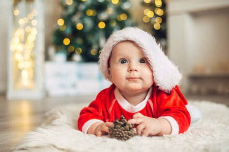 Christmas morning, baby dressed as Santa Claus