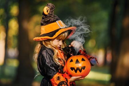 Happy Halloween. Cute little witch with a pumpkin in the hands. Reklamní fotografie - 111082525