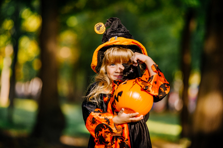 Happy Halloween. Cute little witch with a pumpkin in the hands. Stock fotó - 111082526