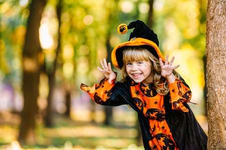 Halloween concept Cute little witch hiding behind a tree in a forest, park. Beautiful girl in witch costume with Halloween decoration. Standard-Bild - 111082527