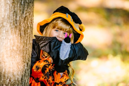 Halloween concept Cute little witch hiding behind a tree in a forest, park. Beautiful girl in witch costume with Halloween decoration. Imagens
