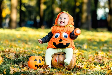 Child in pumpkin suit on background of autumn leaves Stockfoto - 111082530