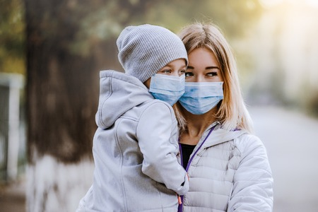 a girl with a child stands on the road in a protective medical mask. Dense smog on the streets. Epidemic of the flu Imagens