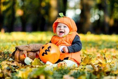 Child in pumpkin suit on background of autumn leaves Archivio Fotografico - 111082537