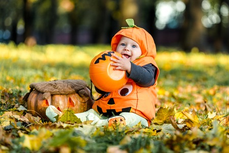 Child in pumpkin suit on background of autumn leaves Stockfoto - 111082538
