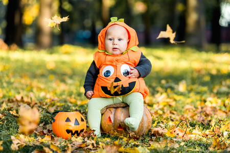 Child in pumpkin suit on background of autumn leaves Archivio Fotografico - 111082539