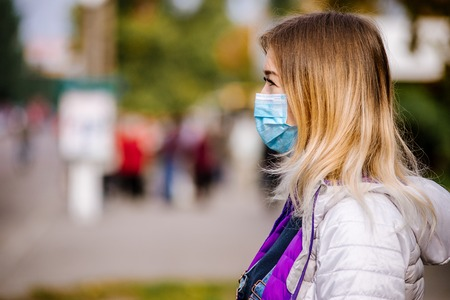 the girl is standing by the road in a protective medical mask. Dense smog in the streets of the city. Stock fotó - 112445728
