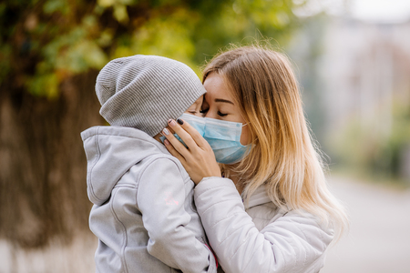 a girl with a child stands on the road in a protective medical mask. Dense smog on the streets. Epidemic of the flu Banco de Imagens