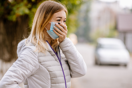 Woman suffering from sick and wearing face mask. Woman in protective mask feeling bad on the street in the city with air pollution. Smog, pollution of the environment.