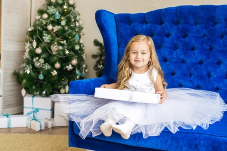 little girl sitting near the Christmas tree with a New Years gift Banco de Imagens