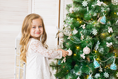 happy girl decorates the Christmas tree Stock fotó