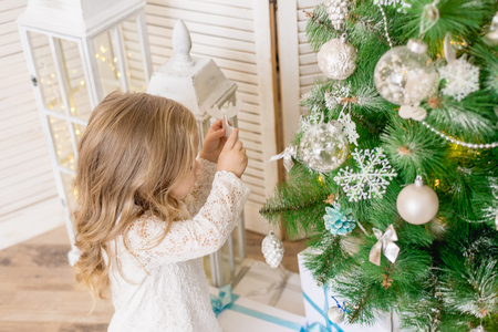 happy girl decorates the Christmas tree 스톡 콘텐츠