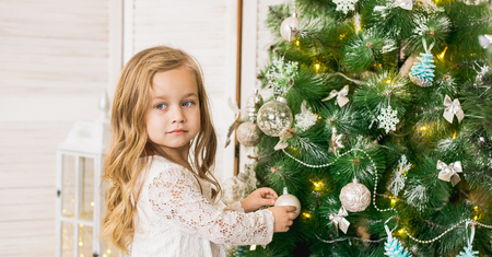 happy girl decorates the Christmas tree 写真素材