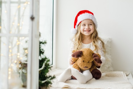 Little girl in the hat of Santa Claus with a plush deer sitting on the window. A child looks out the window and is waiting for Christmas, Santa Claus
