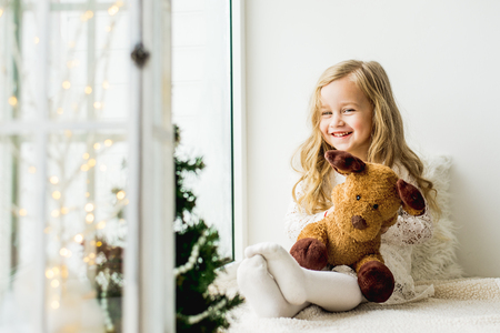little girl with a plush deer sitting on the window. A child looks out the window and is waiting for Christmas, Santa Claus 스톡 콘텐츠