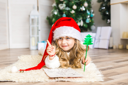 Little girl in Santa hat writes letter to Santa Claus