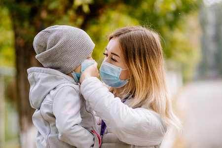 a girl with a child stands on the road in a protective medical mask. Dense smog on the streets. Epidemic of the flu 写真素材