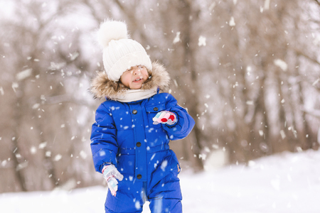 Happy laughing baby girl dressed in a blue thermal suit playing and running in a beautiful snowy winter park on Christmas