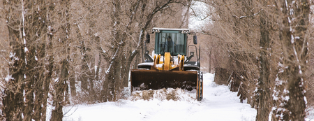 Cleaning the streets of the city from the snow with the help of special machinery bulldozer