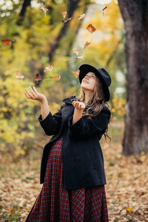 Beautiful autumn girl in the park. Lots of yellow leaves. Girl in a gray coat and red dress. Pregnant girl holding hands belly Stock fotó