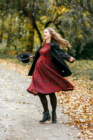 Beautiful autumn girl in the park. Lots of yellow leaves. Girl in a gray coat and red dress. Pregnant girl holding hands belly 스톡 콘텐츠