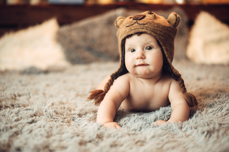 charming baby 6 months lying on his stomach on the bed in a bears cap in the interior 스톡 콘텐츠