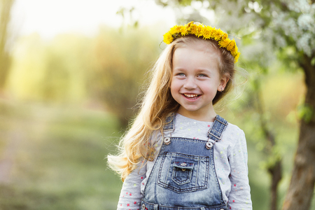Spring sunny portrait of a cute 4 year old girl posing with a dandelion wreath, looking at the camera