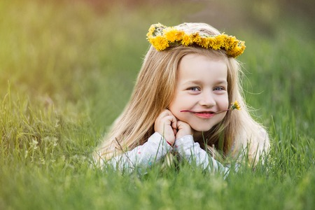 A girl in a wreath of dandelions lying on the grass. Spring concept