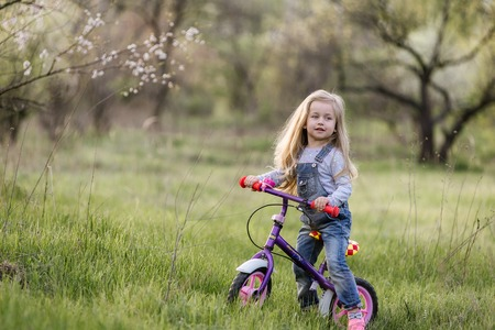 Child riding balance bike. Kid on bicycle in sunny park. Little girl ride glider bike on a warm summer day. Sport for kids