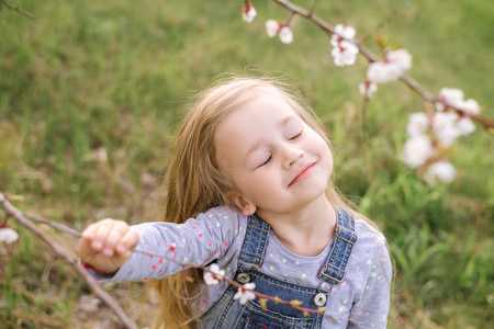 Cute little girl is sniffing blooming flowers in a spring park. Stock fotó