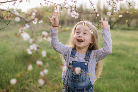 Cute little girl is sniffing blooming flowers in a spring park. Фото со стока